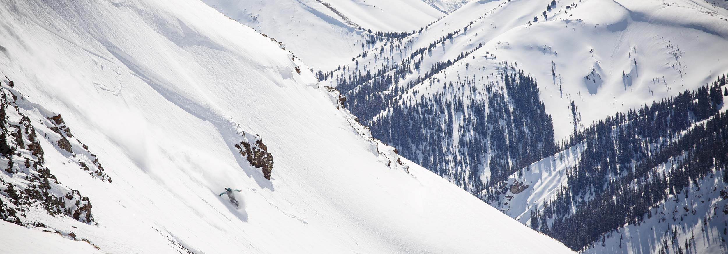 A snowboard experience is engulfed in snow making a toeside turn at Silverton Mountain Colorado
