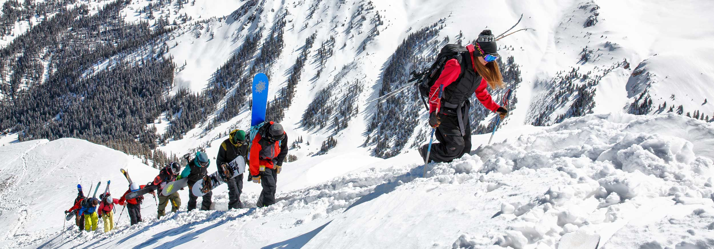 Skiers and snowboarders hike up a ridge at Silverton Mountain Colorado
