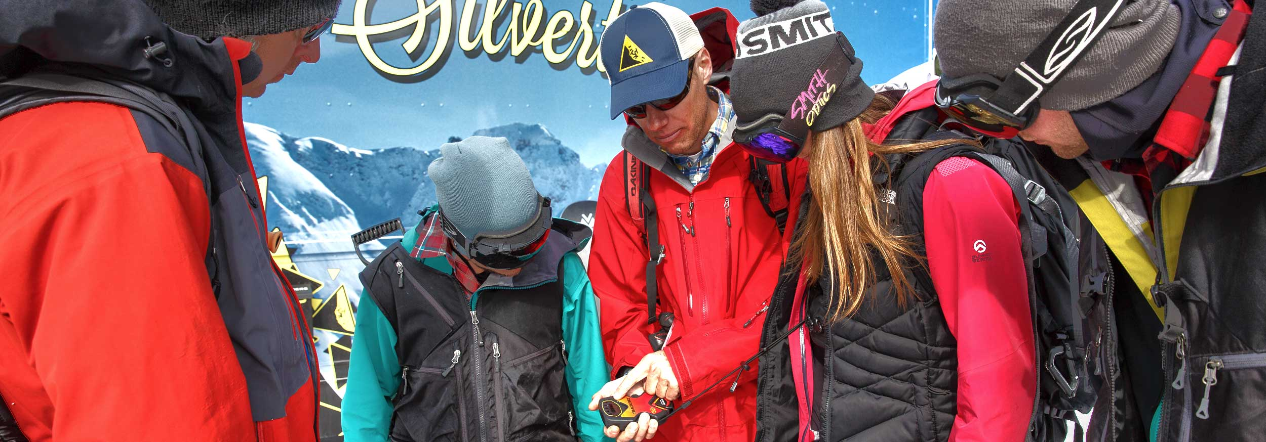 Four clients watch a guide demonstrating how to use an avalanche transceiver at Silverton Mountain Colorado