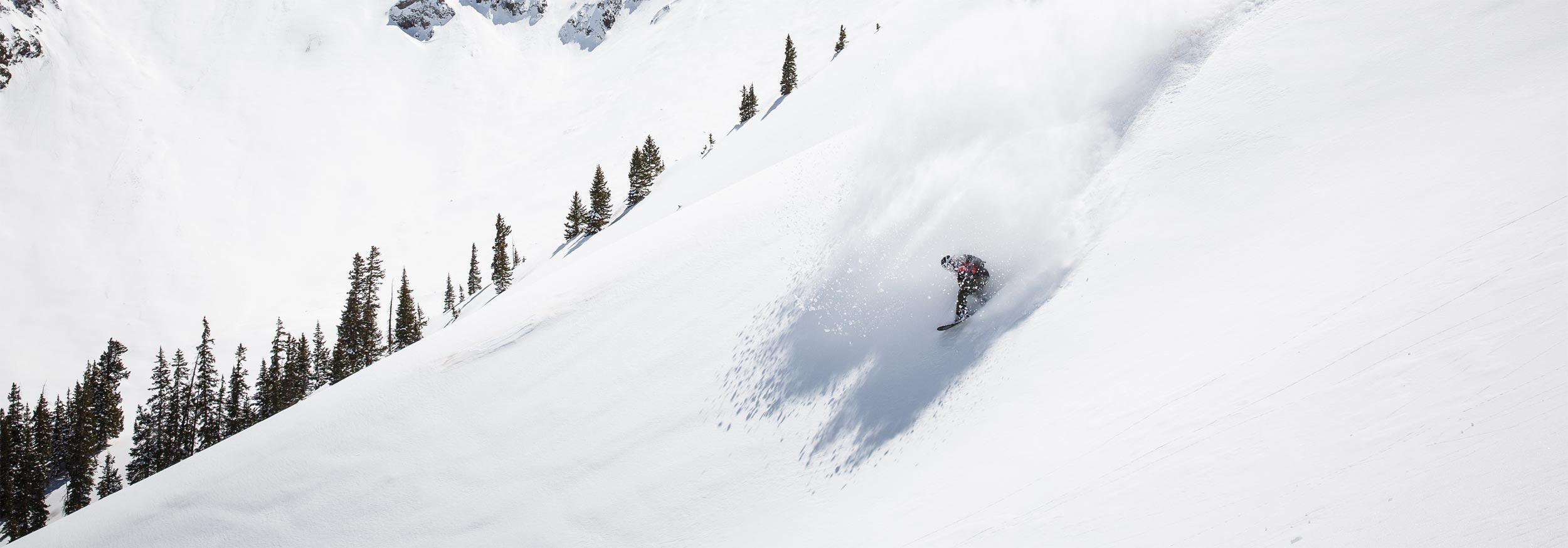A snowboarder makes a turn in powder which exploads in a cloud around him at Silverton Mountain, Colorado