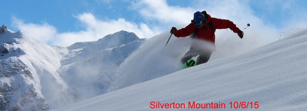 A telemark skier makes a turn with a drop knee. The sky is partly cloudy revealing mountains in the background. Image text says